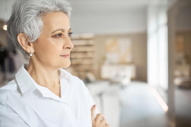 Profilbild der eleganten stilvollen reifen unternehmerin, die weißes formelles hemd trägt, das im modernen büroinnenraum steht