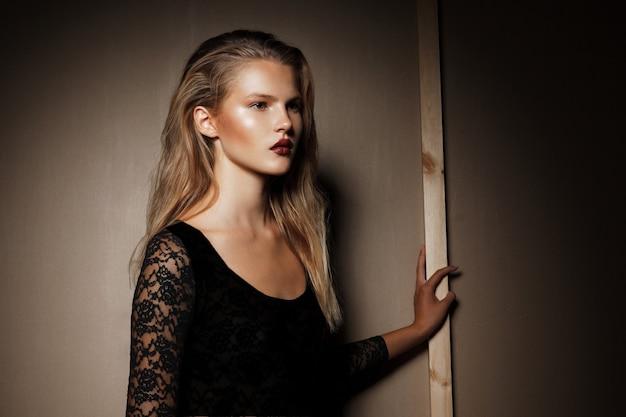 Profilbild eines stilvollen weiblichen modells im schwarzen body mit blonden haaren, das im studio posiert und die seite betrachtet.