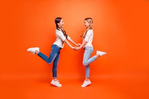 Profilbild in voller größe von positiv fröhlichen zwei kinder mädchen haben freizeit hände halten ruhe entspannen entspannen tragen moderne kleidung weiße turnschuhe isoliert orange farbe hintergrund