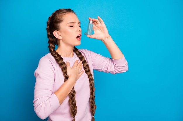 Profilfoto der hübschen dame mit langen zöpfen, die asthmaanfall leiden, unter verwendung des flascheninhalators, um zu stoppen, husten tragen lässigen rosa pullover isolierten blauen farbhintergrund