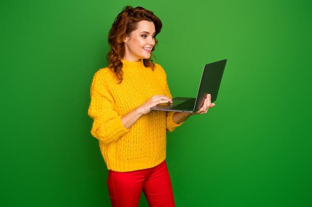 Profilfoto der hübschen fröhlichen dame halten notebook-hände, die freiberuflich it-website-administrator durchsuchen tragen gelben strickpullover rote hosen isoliert grüne farbe wand