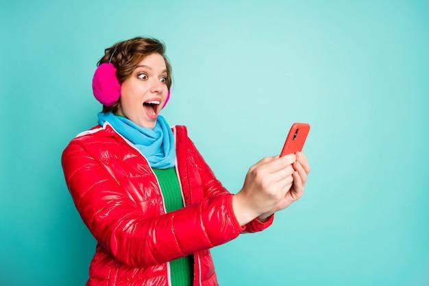 Profilfoto der hübschen verrückten dame mit offenem mund halten telefon lesen gute nachrichten überprüfen mag anhänger tragen roten mantel schal rosa ohrabdeckungen grünen pullover isoliert blaugrün farbe wand