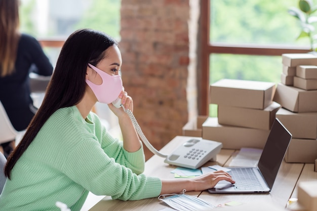 Profilfoto einer asiatischen geschäftsfrau, die medizinische gesichtsmasken organisiert, verpackt lieferboxen, die festnetz-kundenbestelldetails unter hinweis auf informationen notebook-home-office im innenbereich sprechen