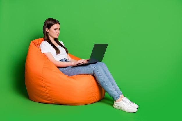 Profilfoto einer attraktiven dame mit computer-sms, die e-mails liest freiberufler tragen t-shirt jeans turnschuhe isoliert auf grünem hintergrund