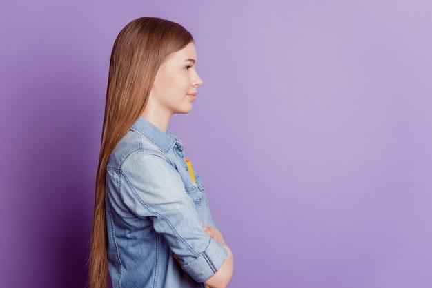 Profilfoto eines entzückenden erfolgreichen mädchens sieht leer aus, gekreuzte hände auf lila hintergrund