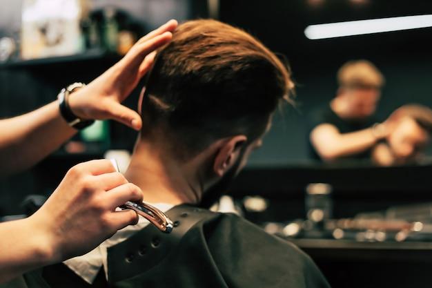 Profilfoto eines jungen friseurs, der in einem friseursalon die haare seiner kunden mit einem elektrorasierer und einem kamm schneidet.