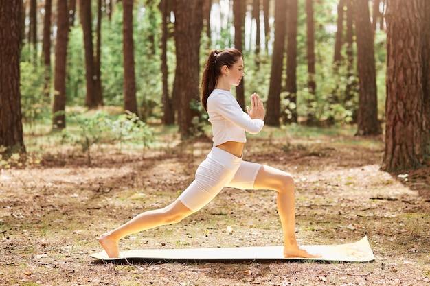 Profilfoto in voller länge der jungen erwachsenen frau mit pferdeschwanz kleidet weiße, stilvolle sportkleidung, die yoga im freien macht, handflächen zusammendrückt, meditiert und sich entspannt.