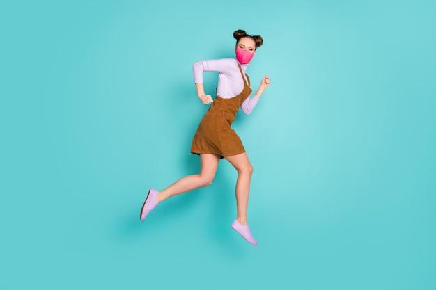 Profilfoto in voller länge von attraktiver dame, die soziale distanz auf der straße führt, vermeiden sie die leute tragen trendige rosa gesichtsmaske mini-braunkleid lila schuhe pullover zwei brötchen isoliert blaugrüner hintergrund