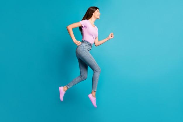 Profilfoto in voller länge von sportlichen süßen mädchen jump run look leeren raum tragen rosa t-shirt sneakers jeans isoliert blauer hintergrund