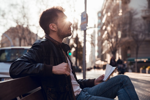 Profilieren sie porträt des mannes mit bart am sonnenuntergang, der auf bank sitzt