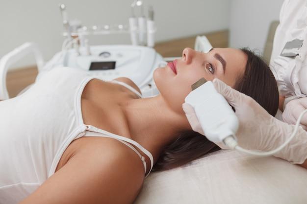 Profilnahaufnahme einer attraktiven frau, die ultraschall-gesichtsreinigung durch kosmetikerin erhält