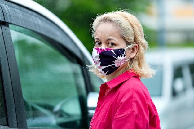 Profilporträt der frau, die eine hausgemachte stoffgesichtsmaske neben einem auto trägt