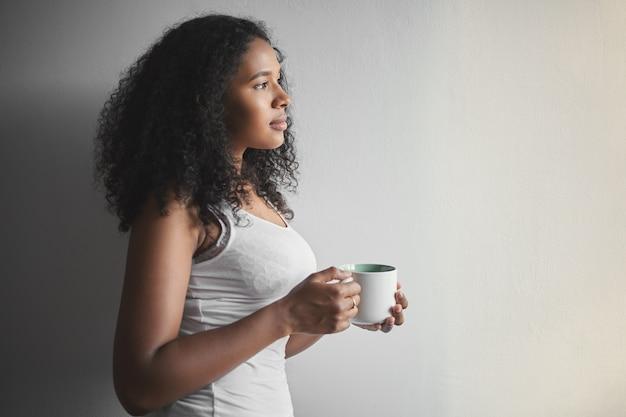 Profilporträt der herrlichen attraktiven jungen mischlingsfrau mit afro-frisur, die becher hält, morgenkaffee vor der arbeit trinkend, gekleidet im weißen trägershirt. menschen, lebensstil, getränke und freizeit