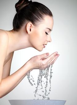 Profilporträt der jungen frau, die ihr gesicht mit sauberem wasser - studio wäscht
