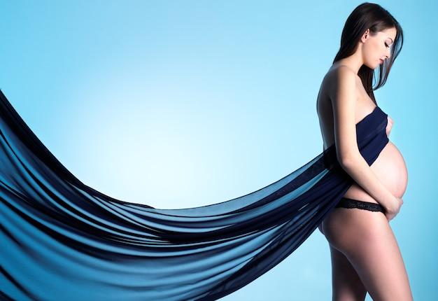 Profilporträt der modischen schwangeren jungen frau mit blauem material auf blau