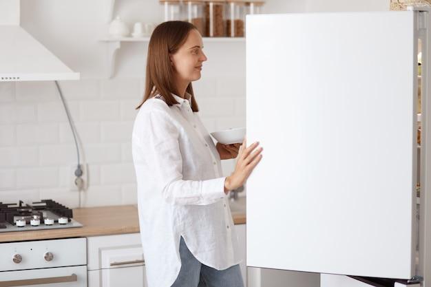 Profilporträt der schönen jungen erwachsenen frau, die weißes hemd trägt, lächelnd im kühlschrank mit angenehmem lächeln schaut, teller in den händen hält und mit küchensatz auf hintergrund posiert.