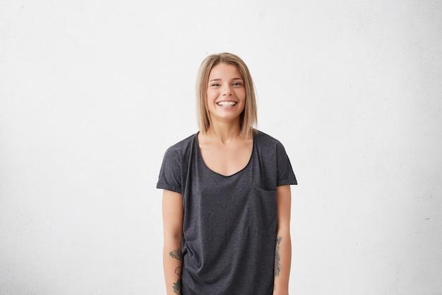 Profilporträt der schönen jungen frau mit blondem hellem haar, das lässiges graues t-shirt mit tätowierungen auf händen trägt, die angenehm lächeln. trendy hipster frau, die gute laune beim aufstellen hat