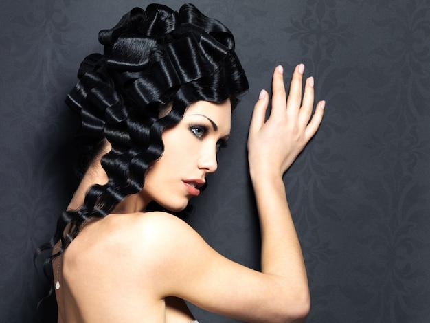 Profilporträt der schönen modefrau mit langer lockiger frisur wirft innen auf