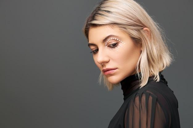 Profilporträt der schönen stilvollen jungen blonden frau im schwarzen transparenten kleid, das lokal betrachtet, das mit traurigem gesichtsausdruck nach unten schaut und sich verärgert fühlt. schüchternes unglückliches süßes mädchen, das nach unten schaut