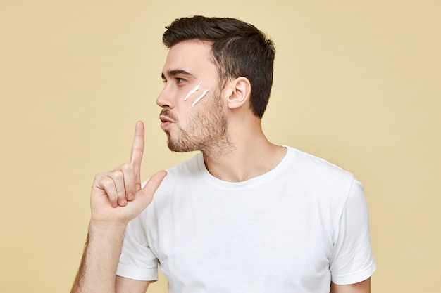 Profilporträt des attraktiven machomannes mit stoppeln und schwarzen haaren, die hand an seinen lippen haltend aufblasen und am zeigefinger blasen, als ob sie psitol verwenden, mit sicherem gesichtsausdruck
