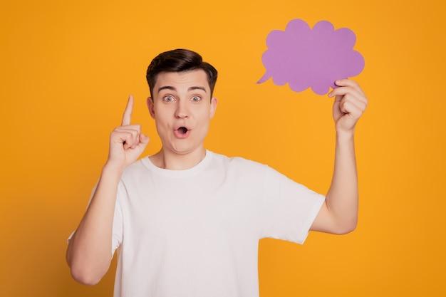 Profilporträt des genialen intelligenten geek-typs, der papierblase hält, hebt den finger auf den offenen mund auf gelbem hintergrund