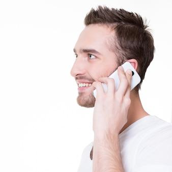 Profilporträt des glücklichen mannes, der durch handy in casuals anruft - lokalisiert auf weiß. konzeptkommunikation.