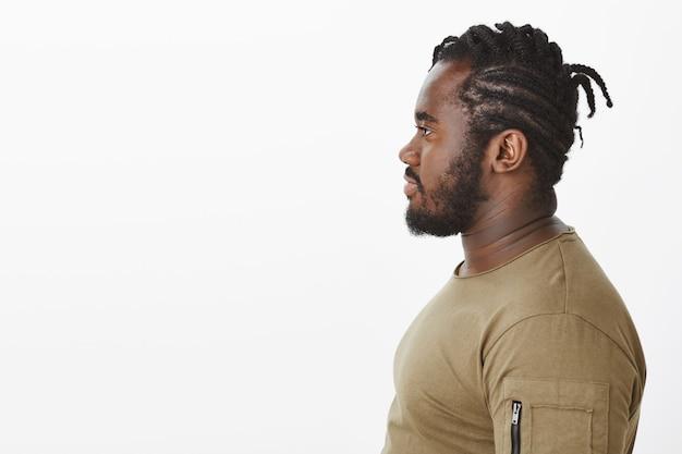 Profilporträt des hübschen kerls in einem braunen t-shirt, das gegen die weiße wand aufwirft
