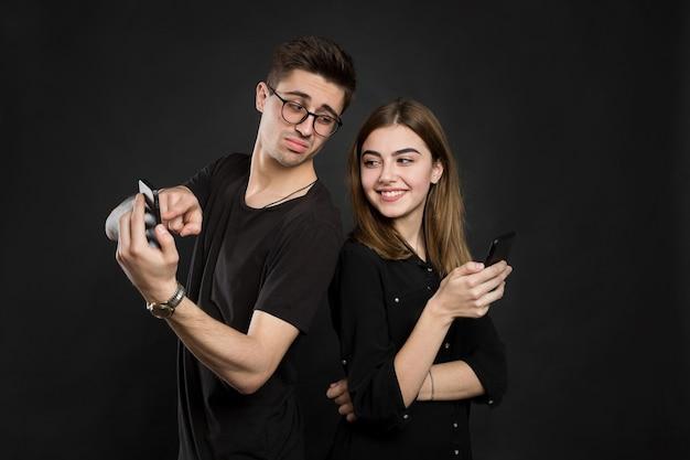 Profilporträt des jungen ehepaares, das informationen an ihren pdas durchsucht, rücken an rücken stehend, lässige outfits auf schwarzem hintergrund tragend.