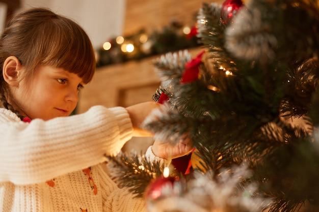 Profilporträt des kaukasischen mädchens, das weihnachtsbaum schmückt, gekleideter weißer pullover, dunkles haar, wartet silvester, ist in festlicher stimmung, frohe weihnachten.