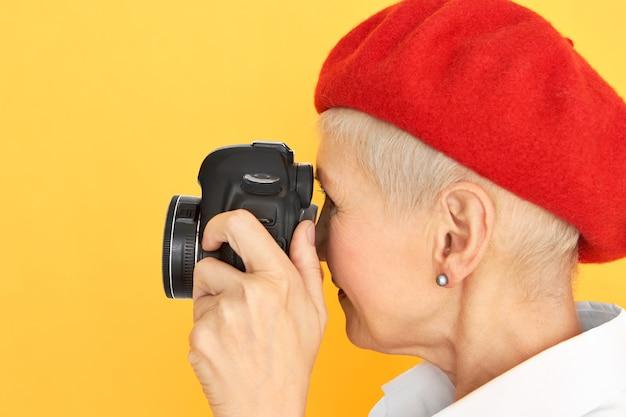 Profilporträt des kreativen stilvollen kurzhaarigen frauenfotografen mittleren alters in der roten haube, die gegen gelben hintergrund mit professioneller digitalkamera in ihren händen aufwirft. kunstfotografie