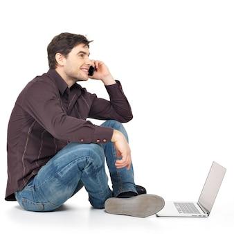 Profilporträt des mannes, der am telefon mit laptop lokalisiert auf weiß anruft.