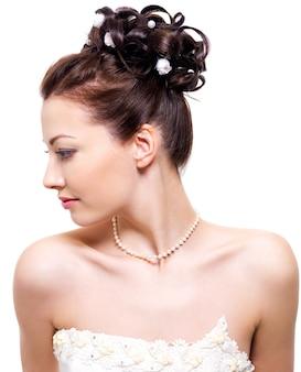Profilporträt einer schönen braut mit hochzeitsfrisur - auf weißem raum