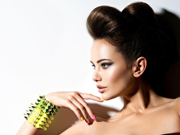 Profilporträt einer schönen frau, die armband mit dornen und mehrfarbigen nägeln trägt