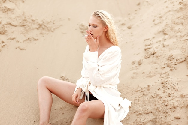 Profilporträt einer sexy jungen blonden frau im weißen hemd, rauchend sitzend auf dem sandboden. porträt im freien.