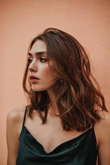 Profilporträt einer wunderschönen jungen dame mit brünetten, welligen haaren, abend-make-up, tätowierung am körper und dunklem seidenkleid, das gegen helle wand posiert