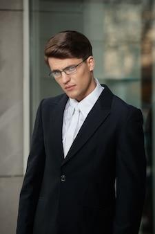 Profilporträt eines gutaussehenden brünetten geschäftsmannes in brillen und schwarzem anzug und weißer krawatte und hemd.