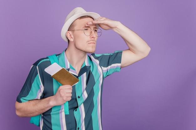 Profilporträt eines interessierten nerd-touristen, der tickets hält, sieht leer aus auf violettem hintergrund