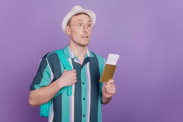 Profilporträt eines neugierigen, charmanten touristentyps, der tickets auf violettem hintergrund hält