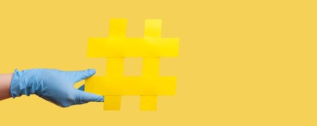 Profilseitenansicht nahaufnahme der menschlichen hand in blauen op-handschuhen mit gelbem hashtag.