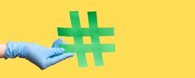 Profilseitenansicht nahaufnahme der menschlichen hand in blauen op-handschuhen mit grünem hashtag.