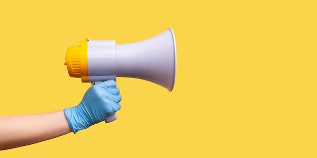 Profilseitenansicht nahaufnahme der menschlichen hand in blauen op-handschuhen mit megaphon.