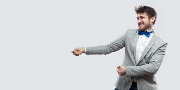 Profilseitenansicht porträt des versuchs gutaussehender bärtiger mann in lässigem grauem anzug und blauer fliege stehend und visualisieren des ziehens. indoor-studioaufnahme, isoliert auf hellgrauem hintergrund.