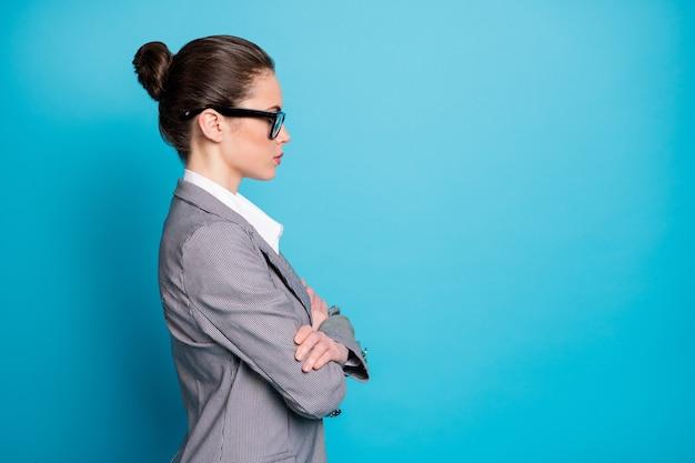Profilseitenansicht porträt einer attraktiven, ernsten, klugen dame mit gefalteten armen kopienraum einzeln auf hellblauem hintergrund