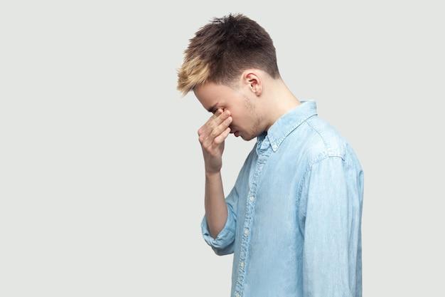 Profilseitenansicht-porträt eines depressiven, traurigen, gutaussehenden jungen mannes in hellblauem hemd, der steht, seine augen bedeckt und weint. innenstudio auf grauem hintergrundkopierraum gedreht.