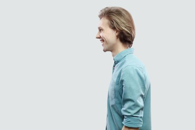Profilseitenansicht-porträt eines glücklichen, gutaussehenden, langhaarigen, blonden jungen mannes im blauen freizeithemd, das mit einem zahnigen lächeln steht und schaut. indoor-studioaufnahme, isoliert auf hellgrauem hintergrund.