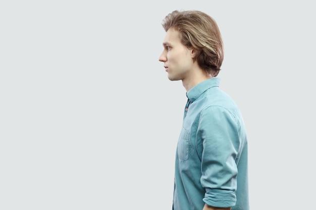 Profilseitenansicht porträt eines gutaussehenden langhaarigen blonden jungen mannes im blauen freizeithemd, das mit ernstem gesicht steht und schaut. indoor-studioaufnahme, isoliert auf hellgrauem hintergrund.