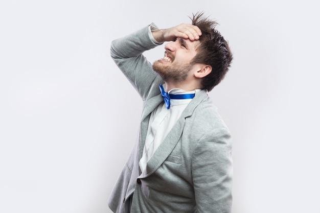 Profilseitenansicht-porträt eines traurigen, gutaussehenden bärtigen mannes in lässigem grauem anzug und blauer fliege, der hoffnungslos steht, weil er alles verliert und sich geirrt hat. studioaufnahme, auf hellgrauem hintergrund isoliert.