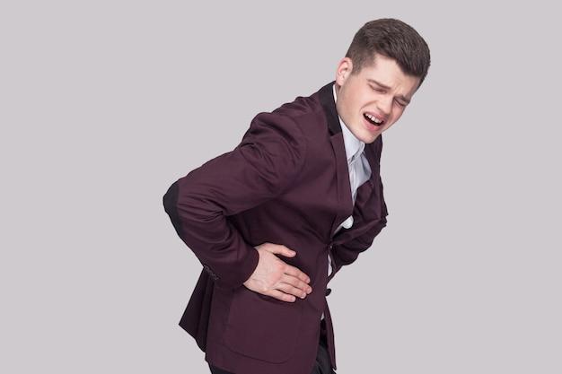 Profilseitenansicht-porträt eines unglücklichen, gutaussehenden jungen mannes in violettem anzug und weißem hemd, der seinen schmerzhaften magen steht und hält und schmerzen verspürt. indoor-studioaufnahme, auf grauem hintergrund isoliert.