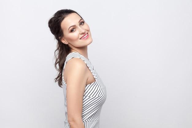 Profilseitenansichtporträt der glücklichen schönen jungen brunettefrau mit dem make-up und dem gestreiften kleid, das steht und die kamera mit einem zahnigen lächeln betrachtet. indoor-studioaufnahme, auf grauem hintergrund isoliert.