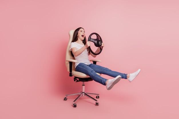 Profilseitenfoto in voller länge erstaunt positives mädchen sitzen stuhl halten lenkrad fahren schnelles auto isoliert rosafarbener hintergrund